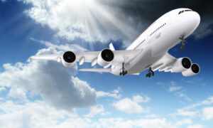 Large passenger plane flying in the blue sky with sun and clouds
