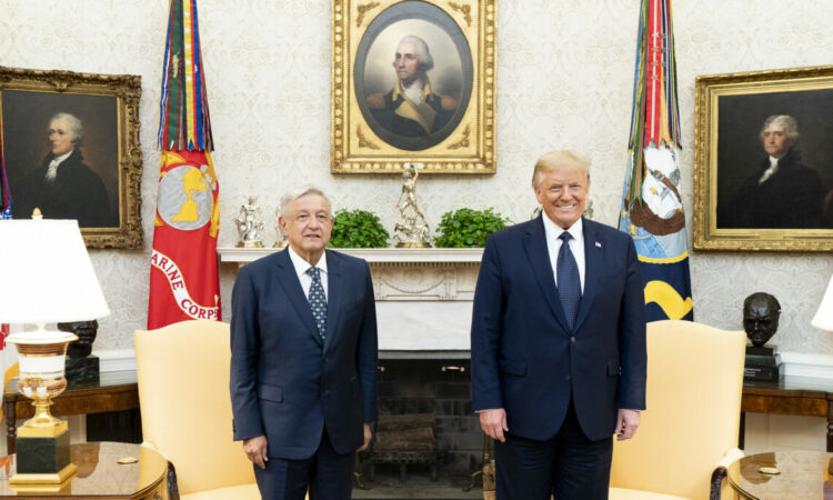 President Lopez Obrador and President Trump stand and smile together indoors.