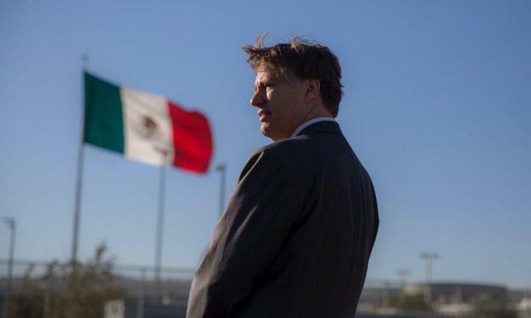 Ambassador Landau stands looking near the Mexican flag