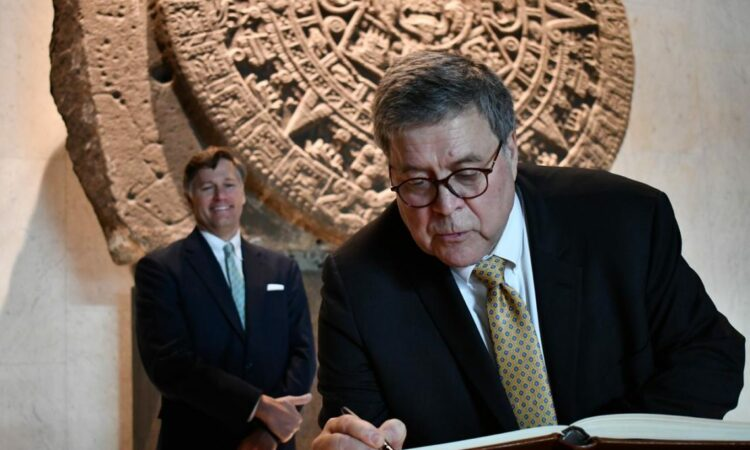 Bill Barr writes his signature in front of an Aztec artifact on the wall