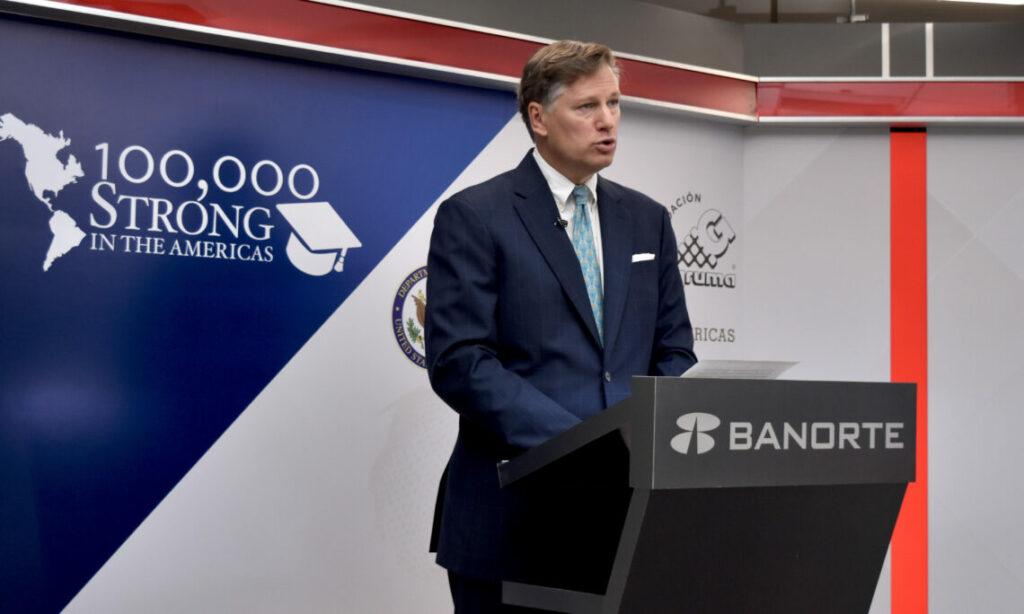 Ambassador Landau speaking in a microphone