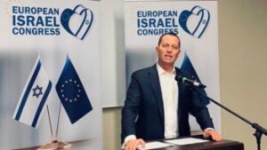 person giving a speech behind a podium in front of European Israel Congress banners