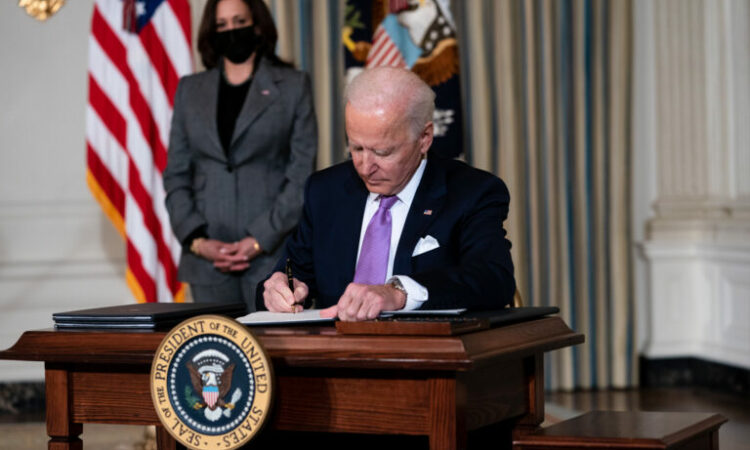 WASHINGTON, DC - JANUARY 26: (L-R) Vice President Kamala Harris looks on as U.S. President Joe Biden signs executives orders related to his racial equity agenda in the State Dining Room of the White House on January 26, 2021 in Washington, DC. President Biden signed executive actions Tuesday on housing and justice reforms, including a directive to the Department of Justice to end its use of private prisons. (Photo by Doug Mills-Pool/Getty Images)