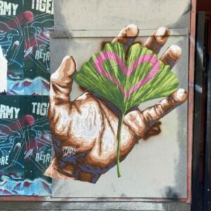 mural of a hand holding a leaf with a heart on it