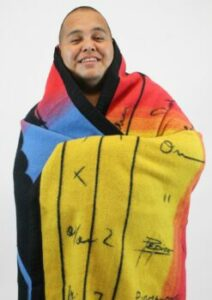 A man wrapped in a multicolored blanket
