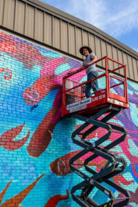 person painting a mural with fish