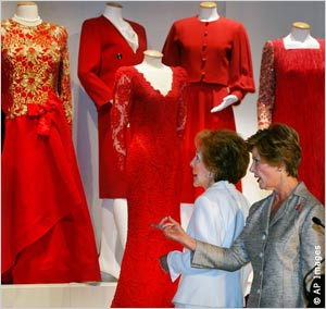 Two women looking at red dresses
