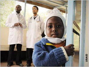 Photo of a toddler with two doctors in the background