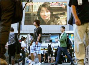 People walking past a street display of the slain journalist