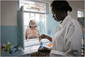 A pharmacist prepares a prescription for a patient outside the window