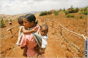 Woman carrying two children