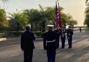 Steven Koutsis Salutes flag with Marines at attention
