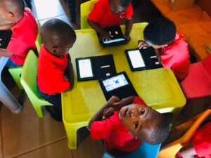 Children sit at table looking at electronics.