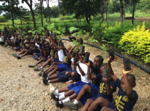 Children sitting in a row holding up tree saplings