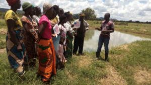 Man teaching a group of people who are standing next to river