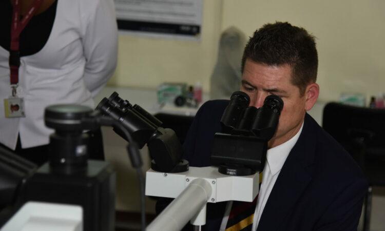 Ambassador McCarter looks into microscope