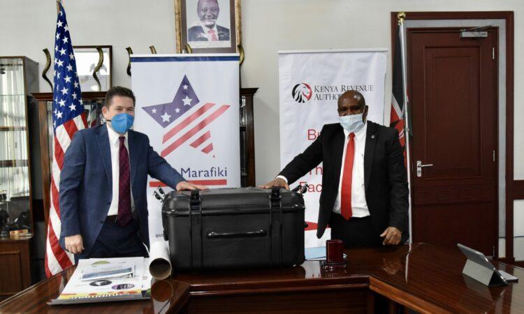U.S. Ambassador Kyle McCarter delivers a training kit for Kenya's front line customs and border control officials to KRA Commissioner General Githii Mburu.
