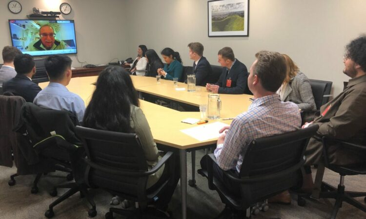 People seated around a conference table. A monitor shows a man, video conferencing into the meeting.