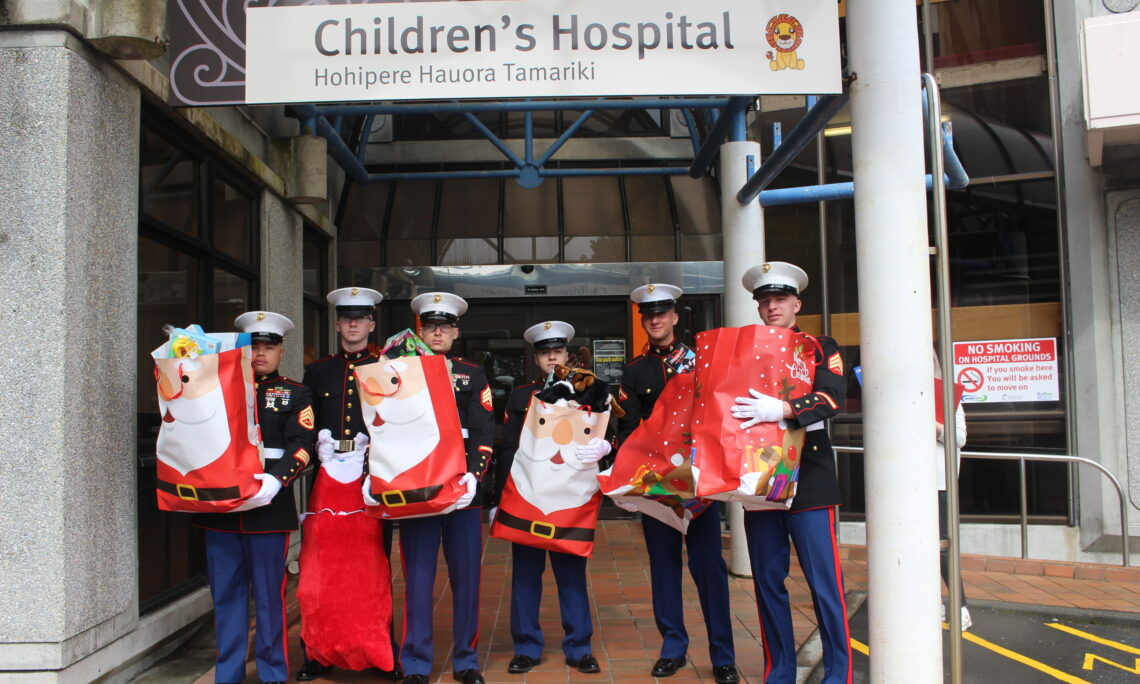 A group of people in uniform hold holiday present bags.