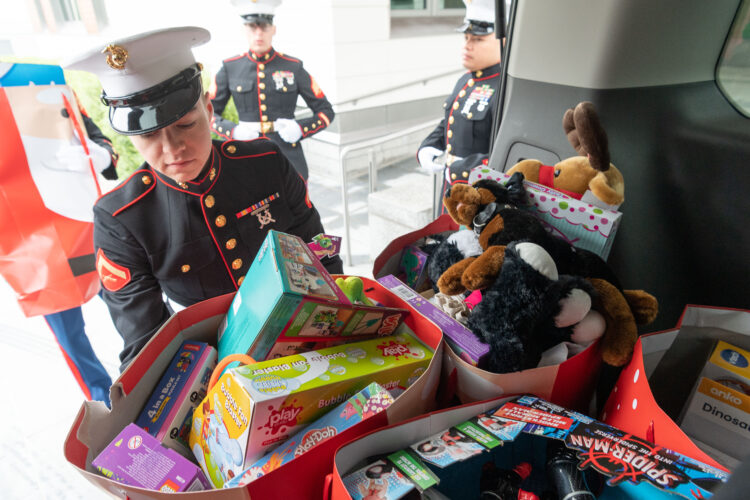 People in uniform load toys in bags into the back of a car.