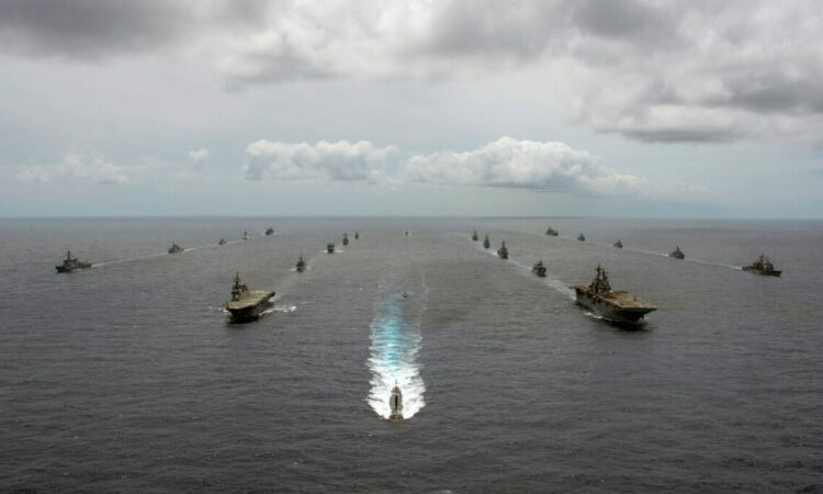 A group of ships in formation in the water.