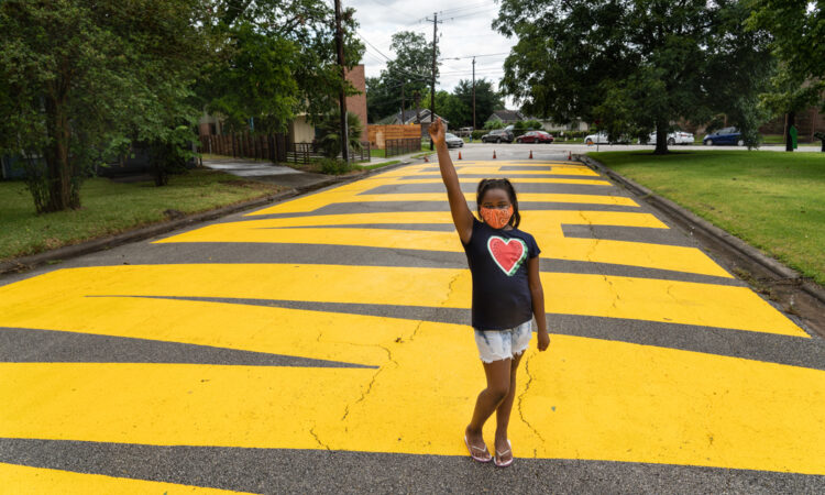 """On June 19, 2020, Kainaan Jones, age 9, poses on """"Black Towns Matter"""" lettering painted on a street in Houston. (© Go Nakamura/Getty Images)"""