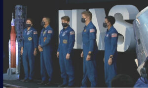 astronauts standing in front of NASA sign