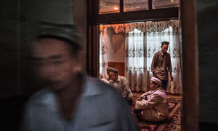 Tuepan, China - Uyghur men gather for a holiday meal during the Corban Festival