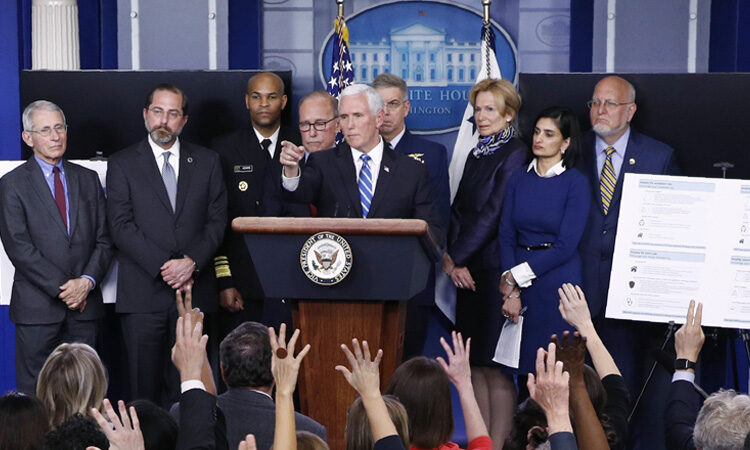 group of people standing behind a podium at a press conference
