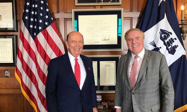 Two men stand together by the U.S. flag and a room full of plaques.
