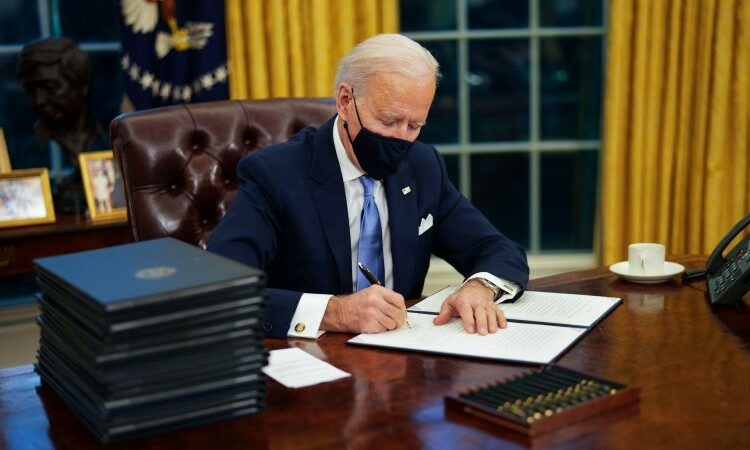 President Biden signs the proclamation on his desk in the oval office