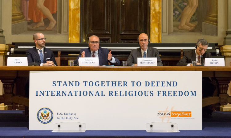 "Four men are seated at a table. Their name tags are in front of them. The banner in front of the table reads ""Stand Together to Defend International Religious Freedom"""