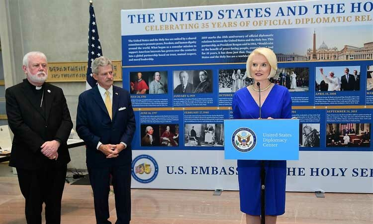 Two men stand off to the left side of the picture. Ambassador Gingrich stands at a podium, speaking to an audience not shown by the picture. Behind her is an informational timeline of diplomatic relations.