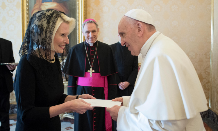 Ambassador Gingrich smiles as she hands papers to Pope Francis. In between the two, but further behind them, you can see a man in religious garb smiling at Pope Francis as well.