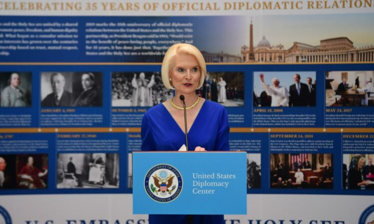 Ambassador Gingrich stands behind a poem, speaking to a crowd not shown in the picture. Behind her is an informational timeline about diplomatic relations.