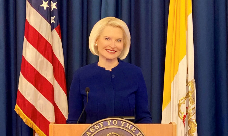 ambassador Gingrich posing for a photo with a blue outfit on and flags behind her