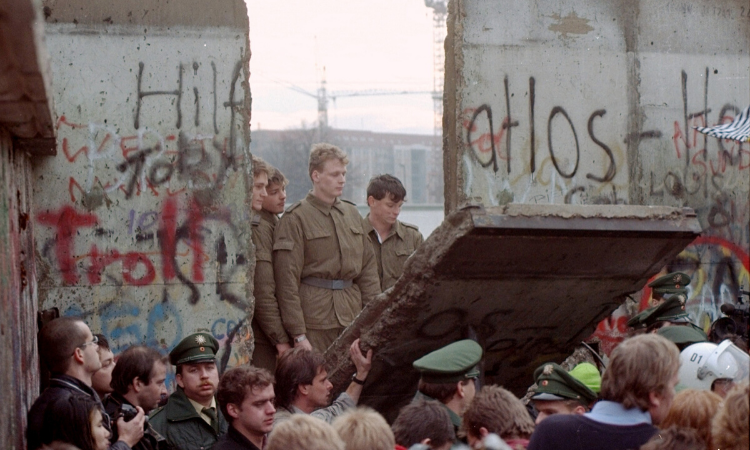 Four soldiers appear through a gap of the Berlin Wall. Graffiti is on the wall. At the bottom of the picture, there is a crowd of people, some removing a part of the wall.