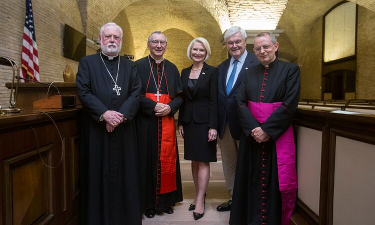 Ambassador Gingrich poses with religious leaders. This event took place indoors, where there are wooden desks and podiums, a TV attached to the wall, and an American flag behind the wooden podiums.