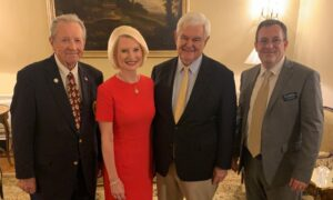 This event took place indoors. Ambassador Gingrich stands with three men, smiling at the camera to take a photo.