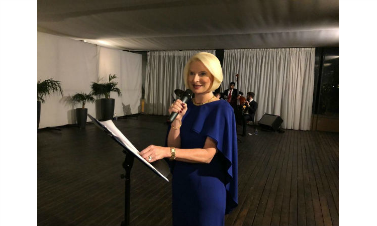 Ambassador Gingrich stands behind a music stand with papers. She holds a hand-held microphone. The jazz band is behind her. This event took place indoors.