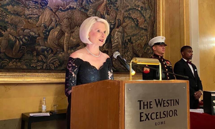"""The sign on the podium reads """"The Westin Excelsior Rome"""". Ambassador Gingrich stands behind the wooden podium and speaks into the microphone. Two men stand off to the side in the background. This event took place indoors."""