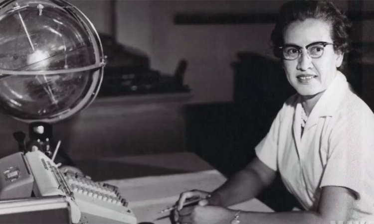 Photo of a woman at a desk with a typewriter and pen
