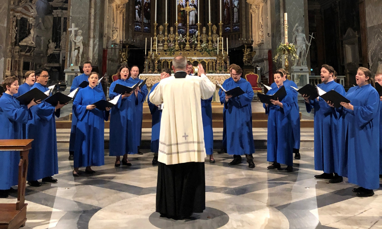The photo shows the back of a priest or other religious leader conducting the choir members that stand in an arc in front of him.