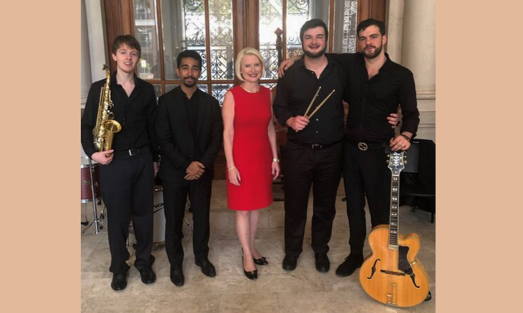 Four members of the jazz band pose with Ambassador Gingrich. One holds a saxophone, another holds his drumsticks, and another has his guitar. Ambassador Gingrich stands in the center.