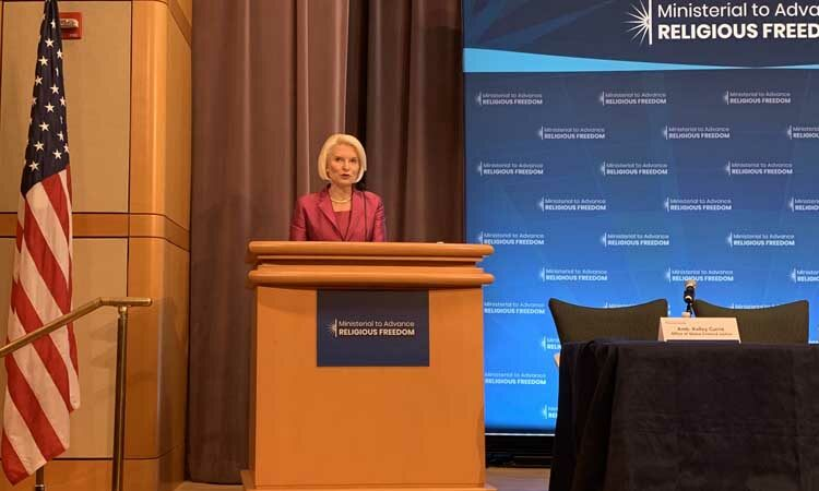 Ambassador Gingrich stands behind a wooden podium, talking. To the right, there is a part of a long conference table. To the left there is an American flag. There appears to be a power point or a projection behind her.