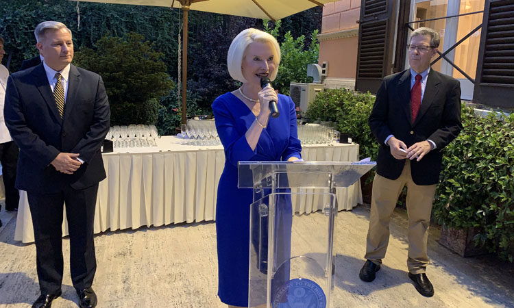 This event took place outdoors in the evening. Ambassador Gingrich stands behind a glass podium with a handheld microphone. Two men stand behind her and at her right and left. Behind her, there is a white table with drinks.