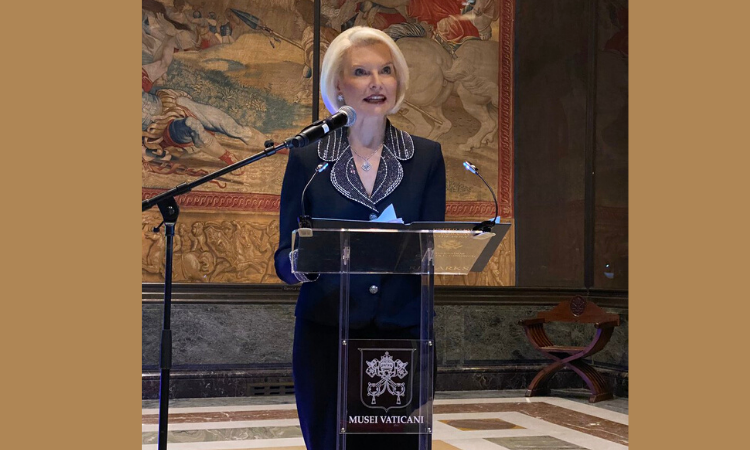 Ambassador Gingrich stands behind a glass podium and in front of an art piece. She speaks into a microphone held up by a mic stand. This event took place indoors.