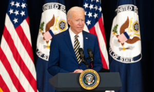 President Biden giving a speech at a lectern with flags behind him